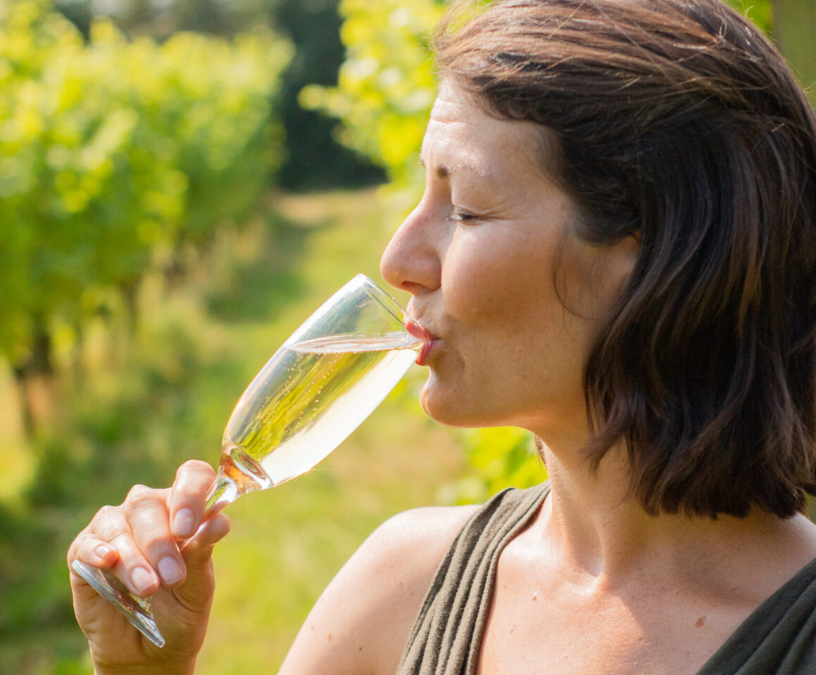 Lady with dark hair sipping from wine glass in a vineyard wine tasting